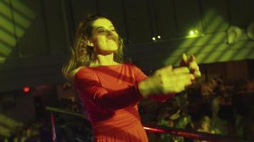 dj fille en robe rouge danse au stand sur la fête en discothèque. projecteur. secouer la tête