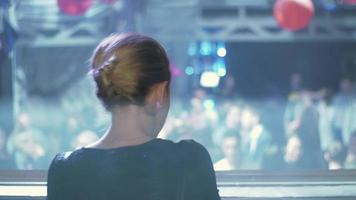 lato posteriore della ragazza dj in top nero danza al giradischi in discoteca. alzare la mano