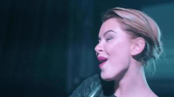 attraente ragazza dj in top nero miscelazione, sorriso, cantando al giradischi in discoteca