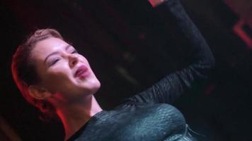 jolie fille dj en noir top clap, chantant à la plaque tournante en discothèque