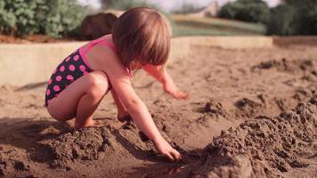 una bambina che gioca nella sabbia in un parco