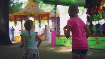 la telecamera segue tre bambine che corrono in un luna park, al rallentatore