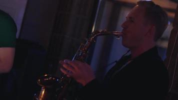 homme joue du saxophone en soirée en boîte de nuit. effectuer. vacances. applaudissement. musicien