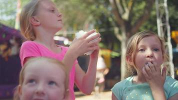 Three little girls eating cotton candy and making funny faces, in slow motion