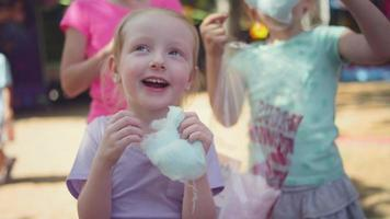 Drei kleine Mädchen essen Zuckerwatte und machen lustige Gesichter in Zeitlupe