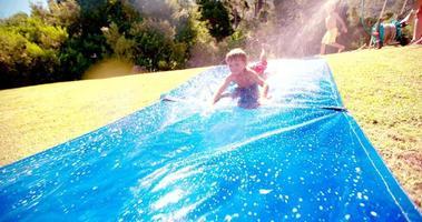ragazzino scivolando verso il basso scivoloso scivolo d'acqua all'aperto video