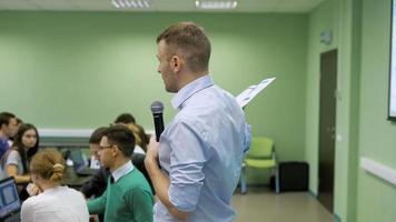 lição de economia em audiência da universidade. alunos vieram para uma palestra. o professor de um seminário explica aos alunos suas tarefas futuras