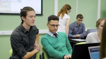 participantes do workshop na classe. menino olhando as informações encontradas na solução do problema do computador, que é colocada na frente deles
