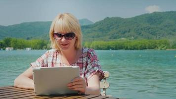 immer verbunden. junge Frau obschaetsya durch die Platte durch eine Videoverbindung. sitzt vor dem hintergrund des malerischen seees und der berge, dem Resort in spanien