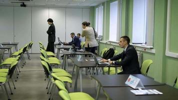 o público para os seminários na universidade. seminário de treinamento para alunos. homem em sua mesa trabalhando em um laptop, está preparando um programa para o workshop