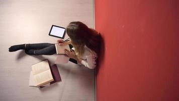 aanhoudend jong studentenmeisje dat op vloer studeert