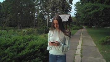 Ein Mädchen in einer Bluse geht auf die Strecke im Park und wird zur Botschaft