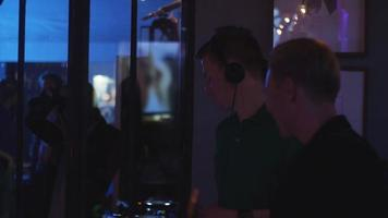 DJ girando na plataforma giratória. homem tocar saxofone. festa na boate. dançando. música