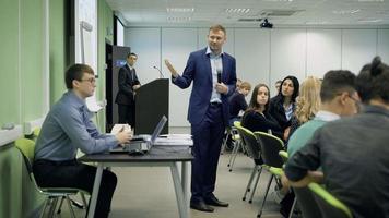 conférencier parle aux étudiants lors d'une conférence sur l'économie.Male gestes de la main et affiche l'image du projecteur