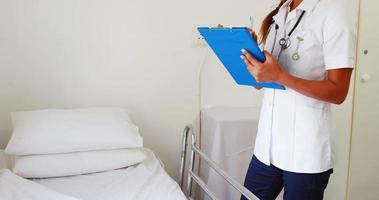 Ärztin mit einem Stethoskop, das im Stehen auf ein Notizbuch schreibt