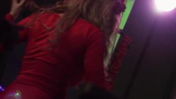 ragazza dj in vestito rosso che gira al giradischi in discoteca. prestazione. battere le mani