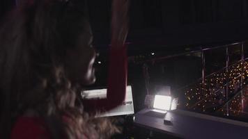 dj garota vestida de vermelho levanta as mãos na plataforma giratória na festa na boate. dançando