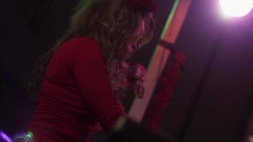 ragazza dj in vestito rosso che gira al giradischi in discoteca. prestazione. alzare la mano