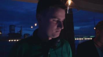 dj com fones de ouvido na plataforma giratória na festa na boate. homem com saxofone. menina
