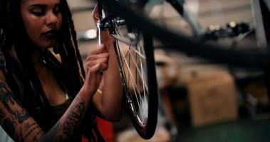 Tattooed female bicycle mechanic working in a repair shop