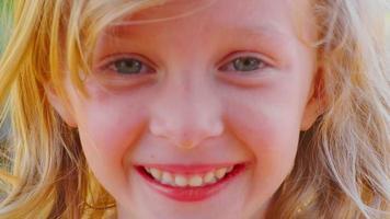 junges blondes Mädchen, das draußen lächelt