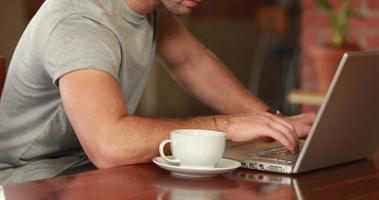 hombre serio hipster trabajando en un portátil