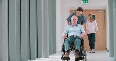 Infirmière poussant un patient senior en fauteuil roulant le long du couloir