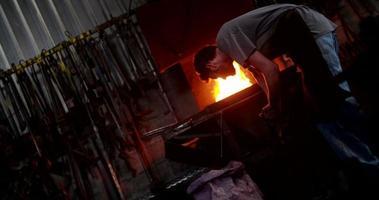 ambachtsman werkende oven in smidse kolen scheppen video