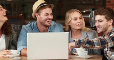 sorridenti amici hipster che ridono su un computer portatile video