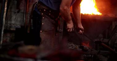 Craftsman working furnace in blacksmith's shop video