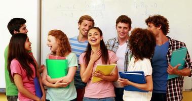 alunos em pé na sala de aula dando polegares para a câmera