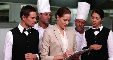 serieus restaurantpersoneel met manager camera kijken
