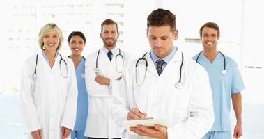 médico escribiendo en el portapapeles mientras el personal está detrás de él