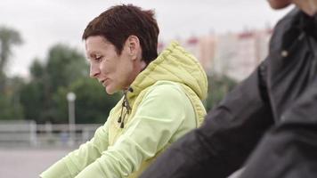 Atleta femenina madura hablando con su colega durante el calentamiento video
