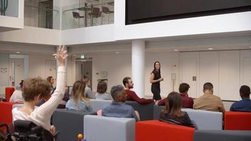 professor apresentando para uma classe universitária, alguns levantando as mãos
