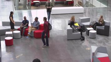 estudantes se socializam e se encontram no saguão de uma universidade, filmado em r3d video