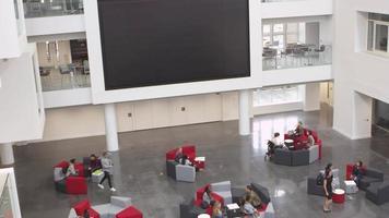 tiro vertical inclinado do átrio da universidade e saguão movimentado, filmado em r3d video