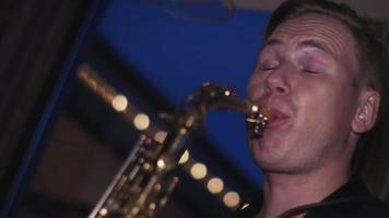 uomo suona il sassofono d'oro sulla festa in discoteca. prestazione. musicista. danza