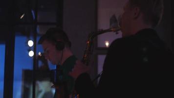 DJ girando na plataforma giratória. homem tocar saxofone. festa na boate. dançando. alegria
