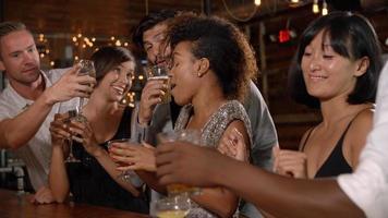 Amigos adultos jóvenes haciendo un brindis en el bar en una fiesta