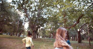 niños pequeños amigables corriendo y persiguiendo burbujas en un parque