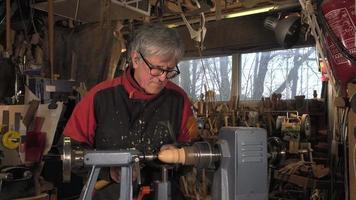 Tourneur sur bois découpant des formes en bois video