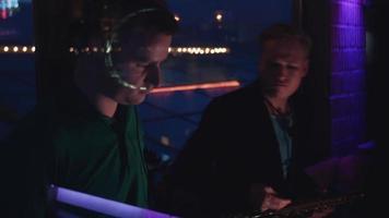 duetto di dj al giradischi e uomo con il sassofono si esibiscono alla festa in discoteca