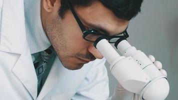 jeune scientifique regardant à travers le microscope