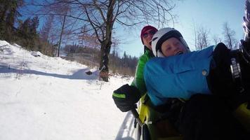 Filmati 4K: padre e figlio sull'attrazione di bob durante le vacanze invernali.