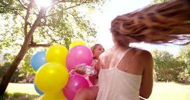 menina feliz e mãe girando em um parque ensolarado com balões em câmera lenta video