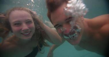 couple souriant en nageant sous l'eau dans une piscine