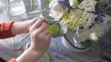 Fleuriste fille mains gros plan faisant une composition de fleurs