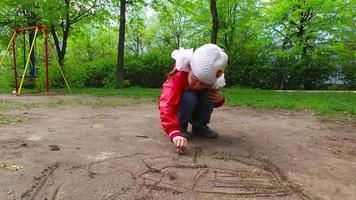 niña niño está dibujando en el suelo. la niña tiene grandes moños blancos.