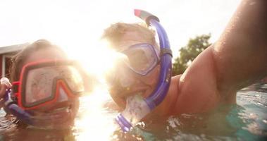 Pareja riendo en la piscina vistiendo equipo de snorkel con destello de lente